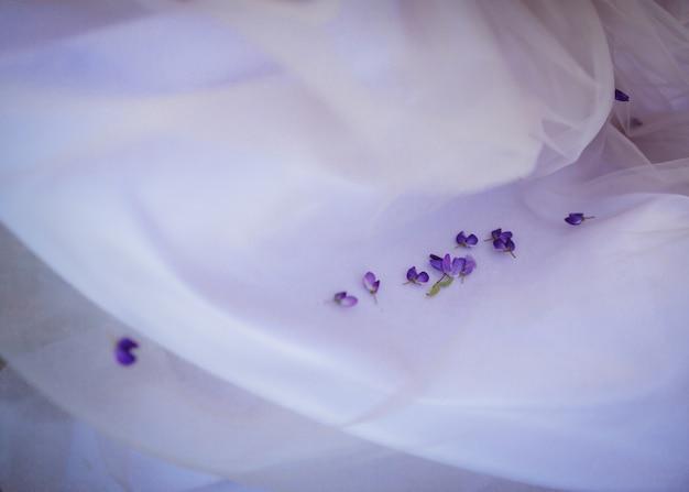 Weinig violette bloemblaadjes liggen op witte doek