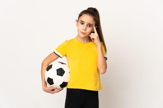 Weinig voetbalster meisje dat op witte achtergrond wordt geïsoleerd die een idee denkt