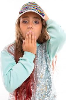 Weinig vrij kaukasisch meisje in een trainingspak behandelt mond met haar hand, beeld dat op witte muur wordt geïsoleerd