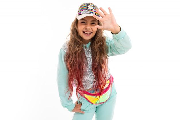 Weinig vrij kaukasisch meisje in een trainingspak golvende hand, beeld dat op witte muur wordt geïsoleerd