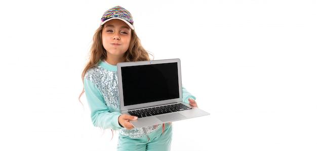 Weinig vrij kaukasisch meisje in een trainingspak houdt nieuwe laptop, panorama dat op witte muur wordt geïsoleerd