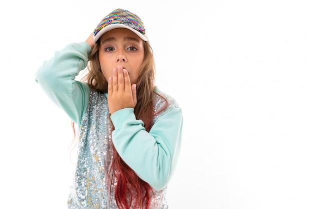 Weinig vrij kaukasisch meisje in een trainingspak is verrast en bedekt mond met haar hand, foto geïsoleerd op een witte muur