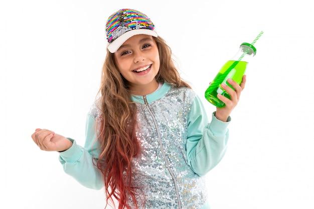 Weinig vrij kaukasisch meisje in een trainingspak met groen sap, beeld dat op witte muur wordt geïsoleerd