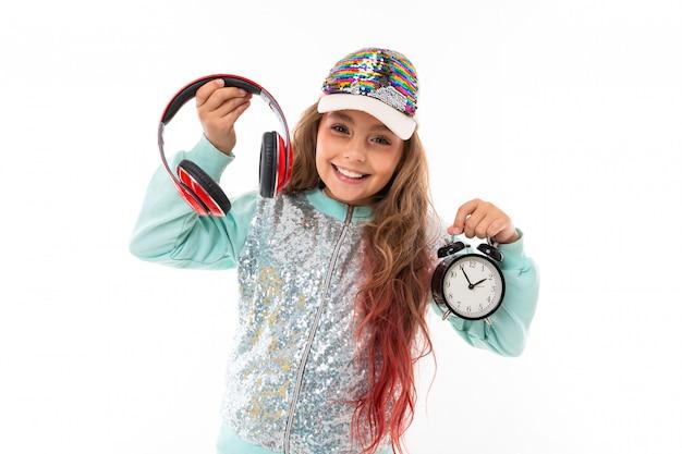 Weinig vrij kaukasisch meisje in een trainingspak met grote oortelefoons en alrmklok, beeld dat op witte muur wordt geïsoleerd