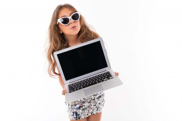 Weinig vrij kaukasisch meisje met zonnebril en laptop, beeld dat op witte muur wordt geïsoleerd