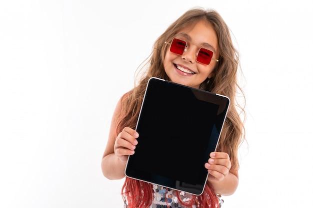 Weinig vrij kaukasisch meisje toont een grote tablet, beeld dat op witte muur wordt geïsoleerd