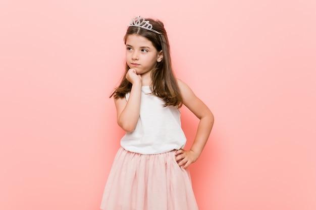 Weinig vrouw die een prinses draagt kijkt zijwaarts met twijfelachtige en sceptische uitdrukking.