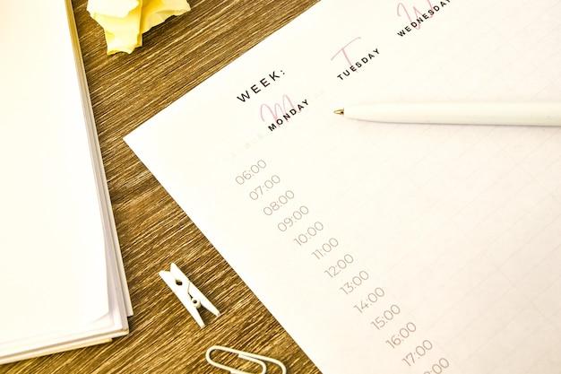 Wekelijkse planner met wekker en kantoorbenodigdheden