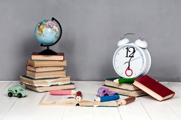 Wekker, boeken, speelgoed en globe op een grijze achtergrond.