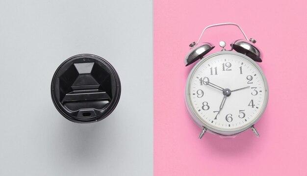 Wekker, container met koffie op roze grijze achtergrond. bovenaanzicht