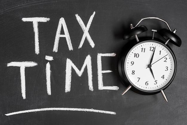 Wekker dichtbij het woord van de belastingstijd dat op zwart bord met krijt wordt geschreven