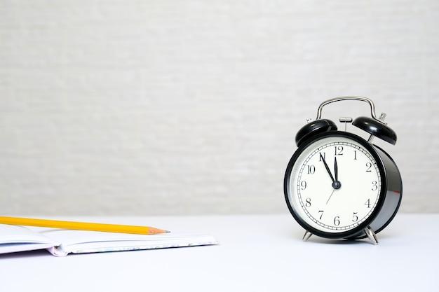 Wekker die 5 minuten voor twaalf en een notitieboekje met een geel potlood als concept de uiterste termijn van het bedrijfsbelastingrapport met exemplaarruimte toont.