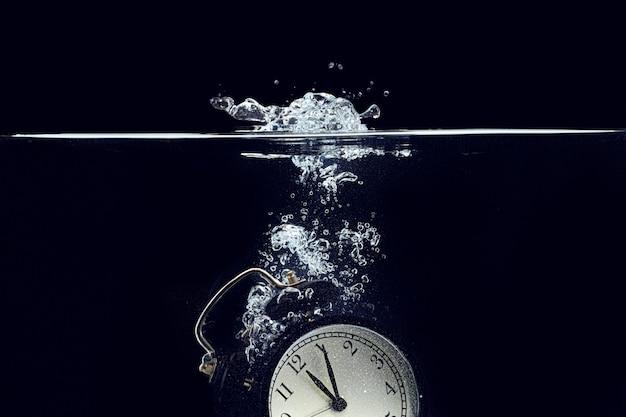 Wekker die in het water valt tegen zwarte achtergrond
