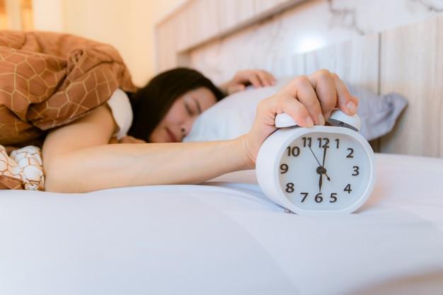 Wekker die 's morgens wakker wordt in de slaapkamer