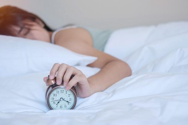 Wekker en aziatische vrouwenhand stoppen tijd in bed tijdens het slapen, jong volwassen vrouwtje wordt laat in de ochtend wakker. fris ontspannen, slaperig en leuke dagconcepten