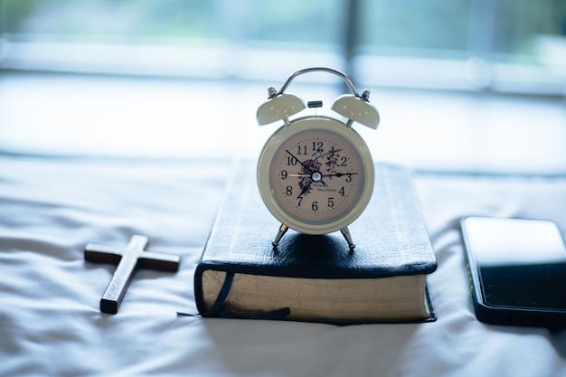 Wekker en de bijbel op bed bereiden zich voor op bijbelstudie.