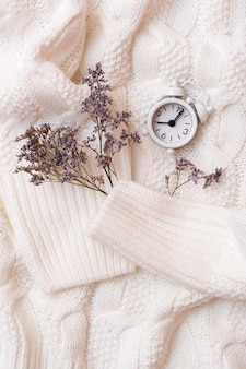 Wekker en droge bloemen op een gezellige witte trui. wellness tijd concept. boven- en verticaal aanzicht