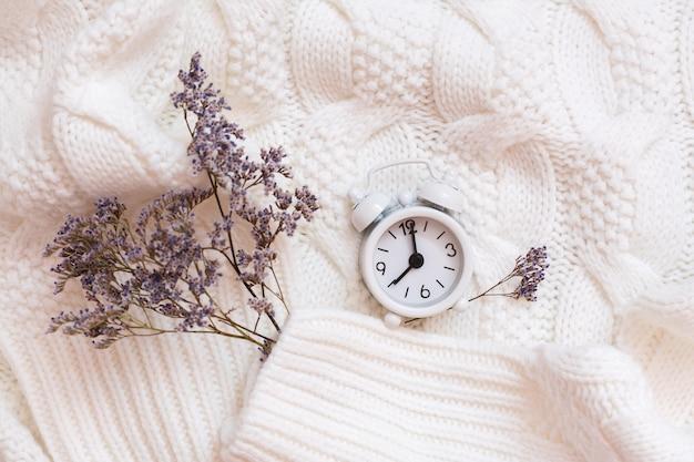 Wekker en droge bloemen op een gezellige witte trui. wellness tijd concept. bovenaanzicht
