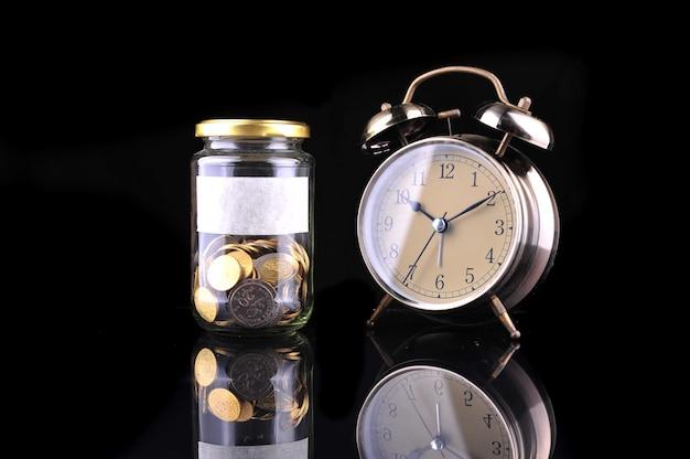 Wekker en fles munten geïsoleerd op zwarte achtergrond