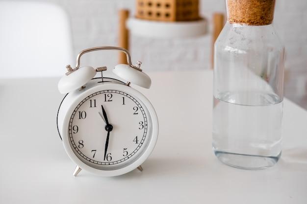 Wekker en glazen fles met water op tafel. tijd om wat water te drinken. dagelijkse gewoonten. goede gewoontes.