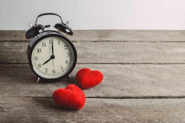 Wekker en hartvorm op houten lijst, de dagachtergrond van valentine