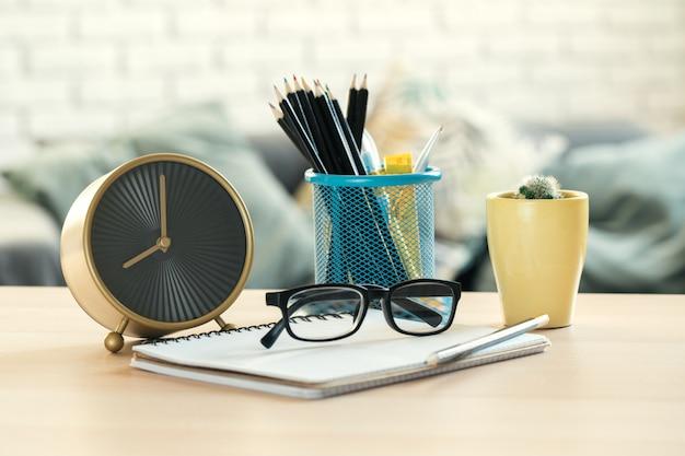 Wekker en kantoorbenodigdheden objecten close-up op houten tafel