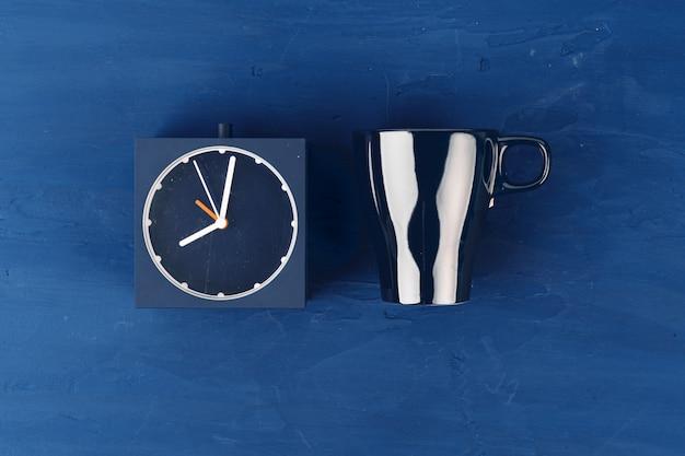 Wekker en keramische klok op klassieke blauwe achtergrond, bovenaanzicht