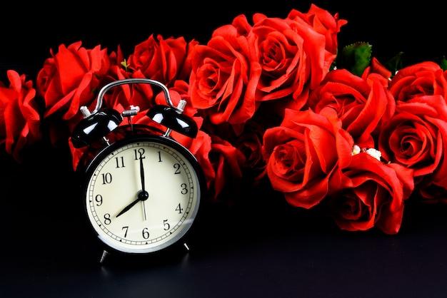 Wekker en rode roos op zwarte achtergrond