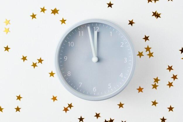 Wekker en sterren confetti. nieuwjaar concept