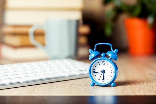 Wekker en toetsenbord op het bureau. office concept, werkdag, uurloon, werkschema.