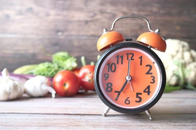 Wekker en verse groenten op tafel met kopie ruimte