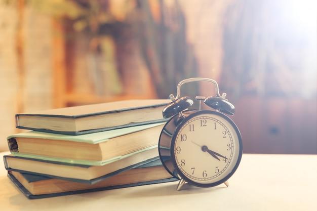 Wekker in de buurt van boeken op de tafel