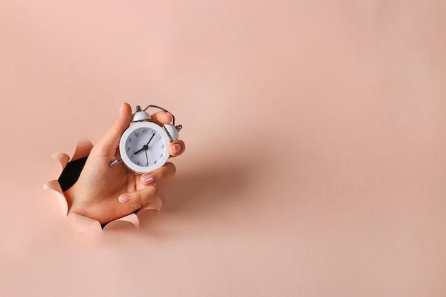Wekker in een vrouwelijke hand die door rond gat in roze document houdt