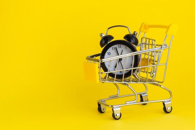Wekker in miniboodschappenwagentje op geel