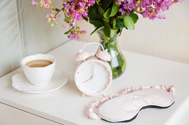 Wekker, kopje koffie en boeket roze bloemen