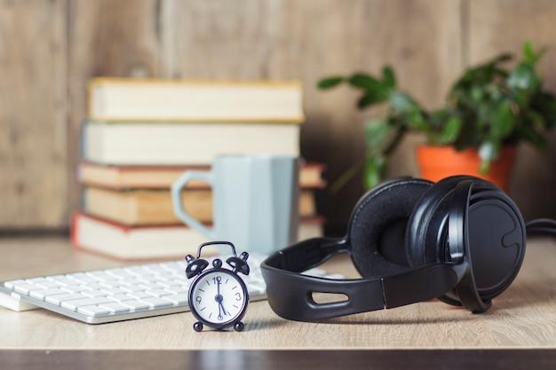 Wekker, koptelefoon en toetsenbord op het bureau met boeken. office concept, werkdag, uurloon, werkschema, werken in een callcenter.