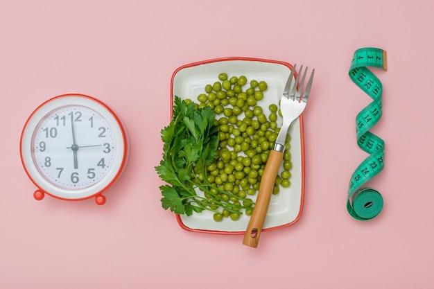 Wekker, meetlint en een bord met groene erwten op een roze achtergrond. het concept van een gezond dieet voor gewichtsverlies.