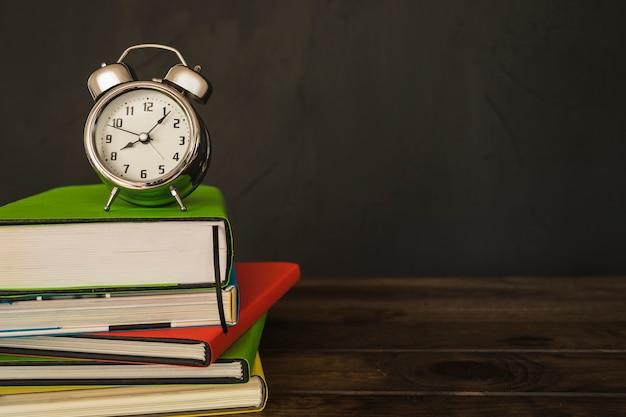 Wekker met boekenstapel op bureau