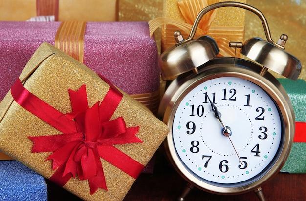 Wekker met kerstboom en cadeautjes op houten tafel close-up