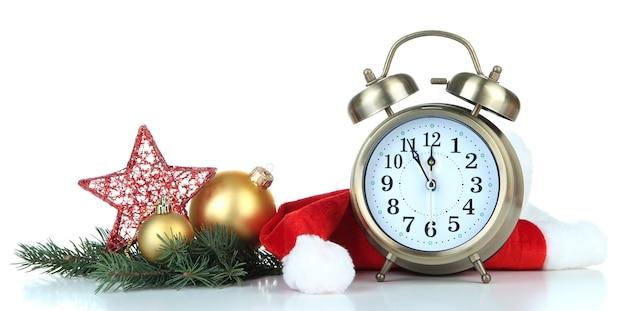 Wekker met kerstmuts en kerstversiering op wit wordt geïsoleerd