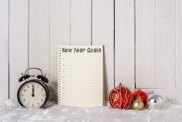 Wekker met kerstversieringen en nieuwjaarsdoelenlijst geschreven op notebook met witte vacht