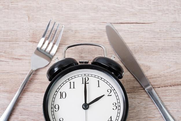 Wekker met mes en vork op houten tafel achtergrond