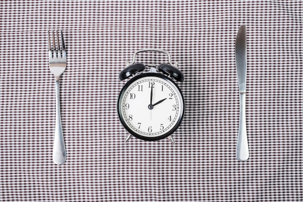Wekker met mes en vork op tafelkleed achtergrond