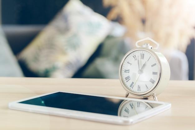 Wekker met mobiele telefoon op een houten tafel