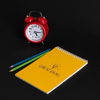 Wekker met notitieblok en kleurpotloden op zwarte achtergrond terug naar school geweldige ideeën