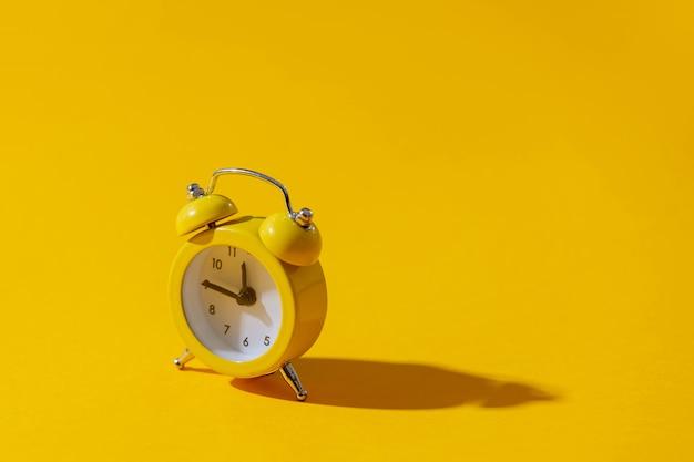 Wekker met twee klokken op gele achtergrond