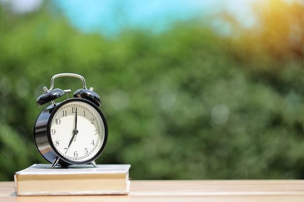 Wekker met wit boek op houten bureau
