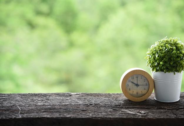 Wekker op de oude houten achtergrond van de de ochtend groene aard van de lijstochtend