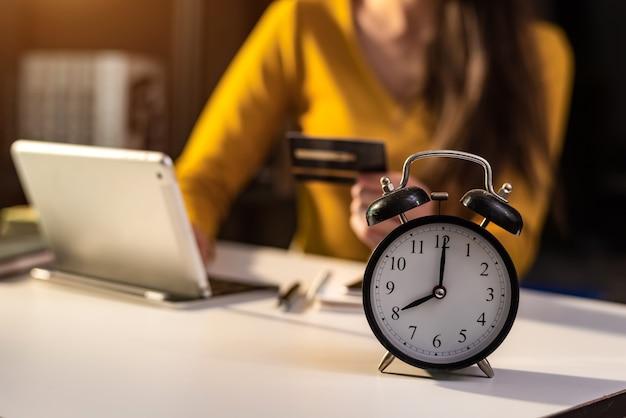 Wekker op het bureau. bedrijf dat 's nachts in een modern kantoorgebouw of thuis werkt met behulp van een laptop.