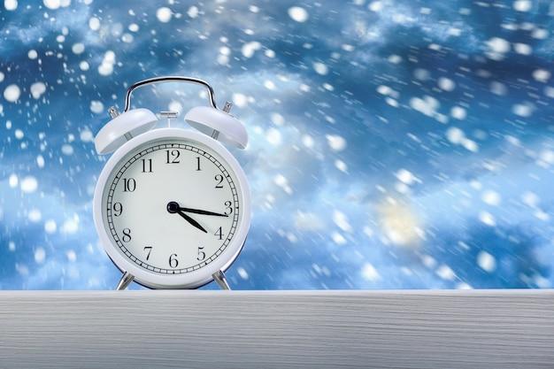 Wekker op houten vensterbank bij sneeuwweer op winterachtergrond. wintertijd concept.